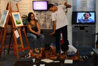 Jovens artistas ministram oficina de pintura com os pés e a boca